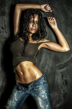 Sexy beautiful woman with long curly wet hair posing over the dark wall, looking at camera. photo