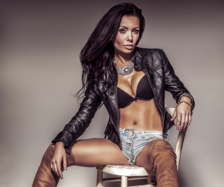 Portrait of sensual brunette woman wearing sexy blackbra and jeans short , posing, looking at camera. photo