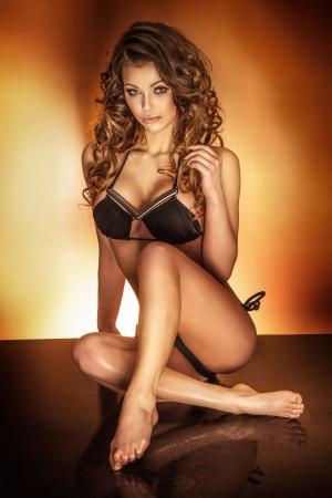 Sensual beautiful brunette woman posing in black lingerie, sitting, looking at camera. Stock Photo - 23735884