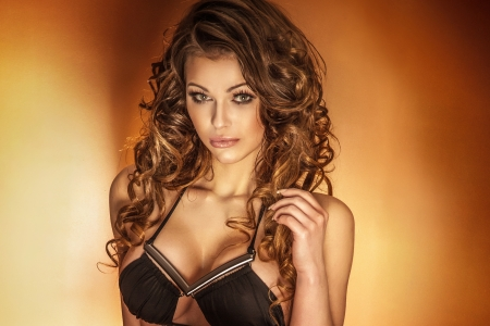 Portrait of beautiful woman with curly long hair looking at camera. photo