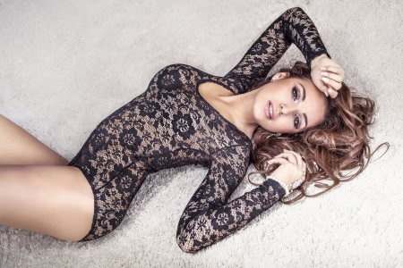 female body: Sensual brunette woman with long hair lying on carpet in underwear, looking at camera. Stock Photo