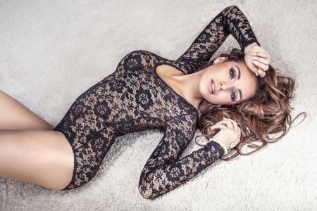 Sensuale donna bruna con i capelli lunghi, sdraiato sul tappeto in mutande, guardando alla fotocamera. Archivio Fotografico - 23735889