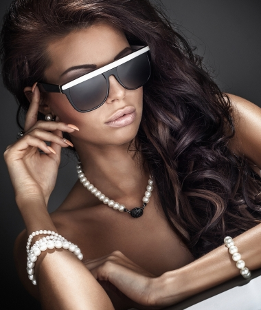 Portrait of beautiful woman with curly long hair wearing sunglasses and jewelry. Standard-Bild