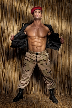 attractive macho: Muscular handsome soldier posing, perfect body. Stock Photo