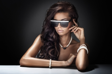 Young beautiful brunette woman posing wearing sunglasses and jewelry. Stock Photo