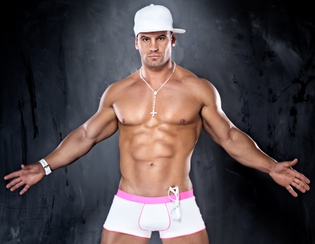 Photo of muscular young handsome man posing in panties, looking at camera. photo