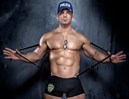 six pack abs: Muscular policeman posing, looking at camera.