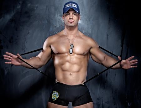 gorra polic�a: Posando polic�a muscular, mirando a la c�mara.