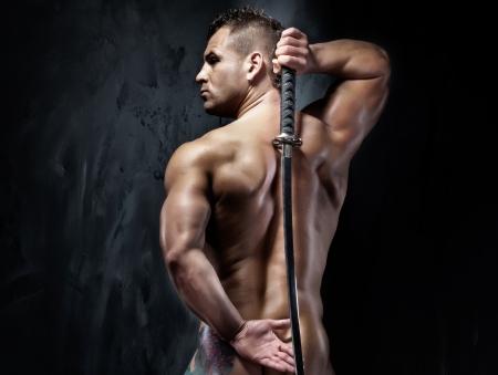 hombres sin camisa: Apuesto joven posando con la espada samurai. Foto de archivo