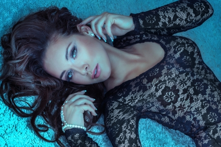 ojos marrones: Retrato de una atractiva joven morena mujer acostada, mirando a la cámara. El pelo rizado largo.