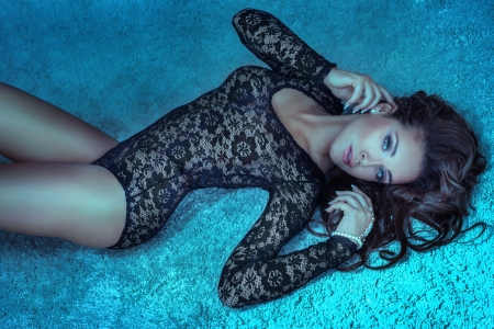 Sensual brunette woman with long hair lying on carpet in underwear, looking at camera. photo