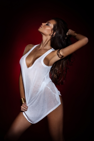 Attractive brunette woman with long curly hair posing wearing white shirt.