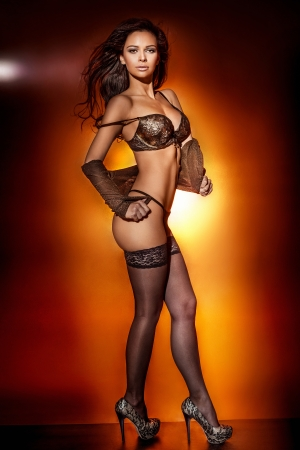 Sexy brunette woman standing, posing in black sensual lingerie. Stock Photo