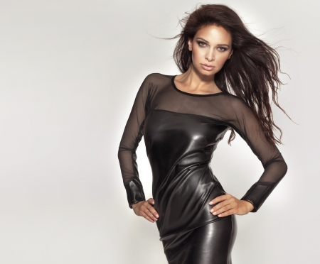 Fashion brunette woman posing in black dress looking at camera. photo
