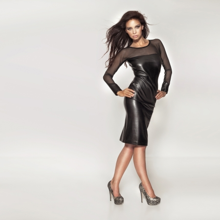 Fashion brunette woman posing in black dress looking at camera.