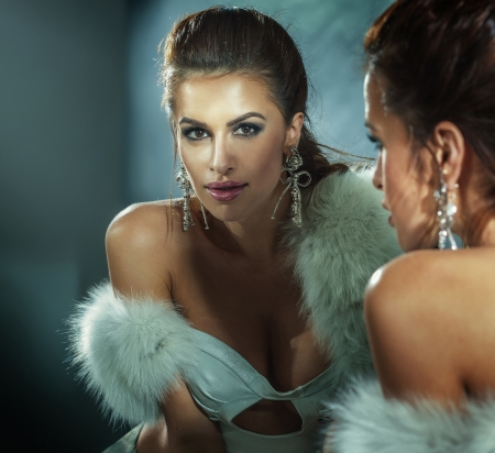 Sexy brunette woman posing wearing white fur and elegant jewelry. photo