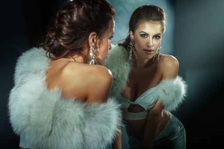 Sensual brunette woman posing wearing white fur, looking at the mirror. photo