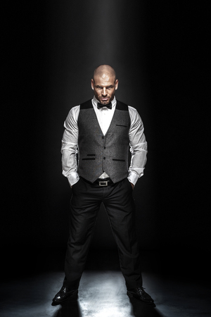 Fashion shot of an elegant young man wearing suit on black background. photo