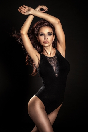 Beautiful young brunette woman with long curly hair dancing over black backround. photo