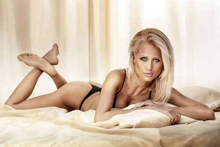Beautiful sexy blonde woman lying, looking at camera. photo