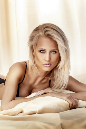 Beautiful portrait of sexy blonde woman lying, looking at camera. photo