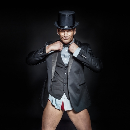 Cheerful elegant handsome man posing in suit, hat and panties, looking at camera. photo