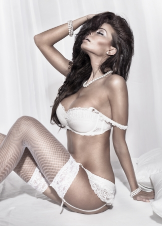 Sensual brunette woman posing in white sexy lingerie. Girl in bedroom. photo