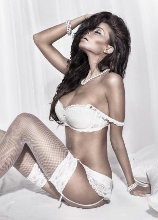 seni: Sensuale donna bruna posa in bianco lingerie sexy. Ragazza in camera da letto.