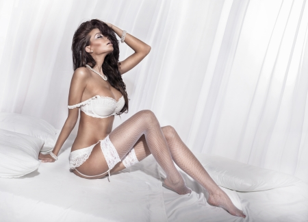 Sensual brunette woman posing in white sexy lingerie. Girl in bedroom.