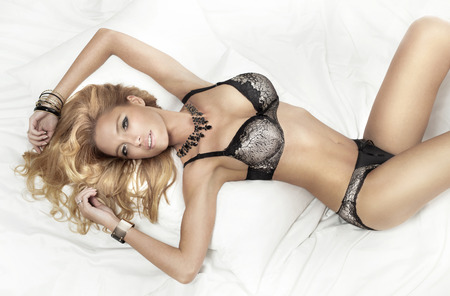 Sensual blonde woman posing in fashion lingerie, lzing on big white bed. photo