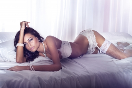 Attractive sexy brunette woman lying in bed wearing white sensual lingerie.