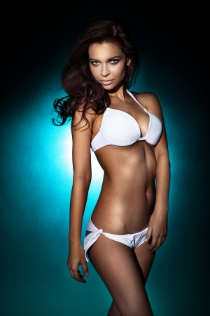 Sensual brunette woman posing in white swimsuit. Studio shot.