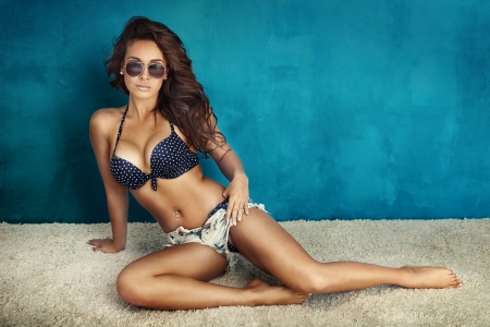 Summer photo of beautiful brunette woman posing in sunglasses and wearing swimsuit. photo