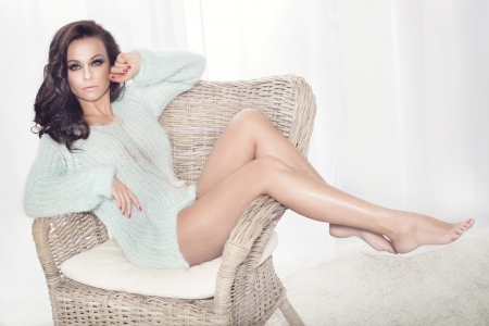 Gorgeous beautiful sexy brunette woman sitting on chair photo