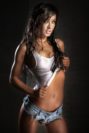 Sensual brunette woman posing with long wet hair. Studio shot. photo