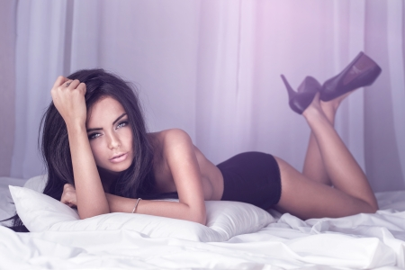 sexual: Sensual brunette woman posing in big white bed. Studio shot.