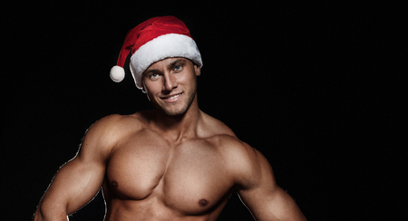 handsome muscular young man in Santa Claus hat at Christmas. photo