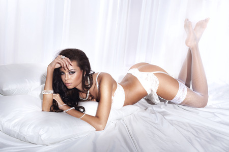Sexy brunette woman posing in big white bed, lying. Attractive beauty wearing sensual lingerie and jewelry. photo