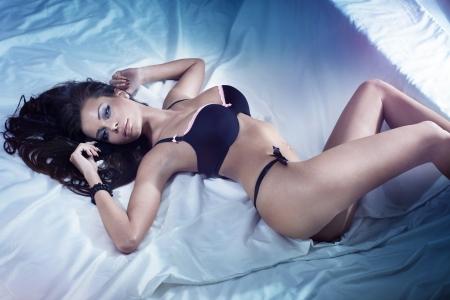 hot breast: Красивая сексуальная брюнетка молодая женщина, ношение черного белья в постели. Мода стрелять белье в помещении.