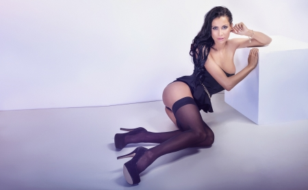 brunette naked: Sexy brunette woman posing in sensual lingerie, looking at camera. Studio shot.