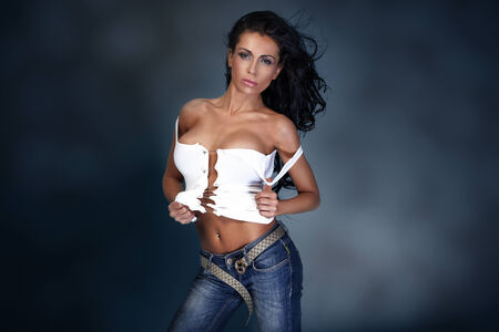 Fashion photo of attractive young brunette girl wearing jeans photo