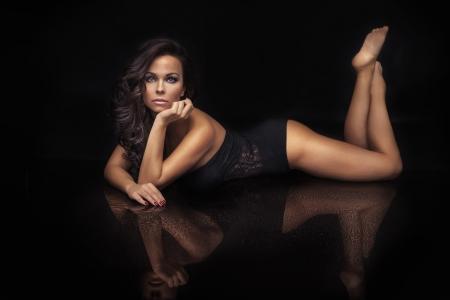 sexy nackte frau: Sch�ne elegante Br�nette Frau posiert in schwarzen Dessous, liegend, sich mit Kamera Lizenzfreie Bilder
