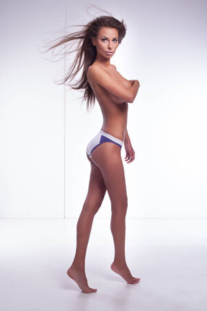 nude woman standing: Sexy brunette woman posing sexy in studio, looking at camera. Beautiful lady with perfect fitness body Stock Photo