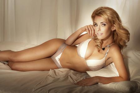 sexy girl nue: Sexy femme blonde sensuelle en lingerie couch�, de d�tente. Banque d'images