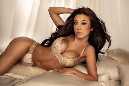 seni: Beautiful sexy brunette donna elegante in posa in lingerie, guardando alla fotocamera.