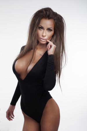Delgado mujer morena sexy posando con ropa interior negro, mirando a la cámara.