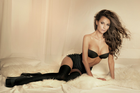 Romantic beautiful brunette woman posing in bedroom wearing lingerie , looking at camera photo