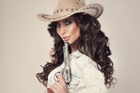 Portrait of sexy brunette cowgirl with revolver, looking at camera.