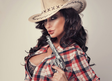Portrait of sexy brunette cowgirl with revolver, looking at camera. photo