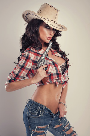 sexy breasts: Sexy brunette woman with amazing hair in hat. Beautiful cowgirl in studio. Stock Photo